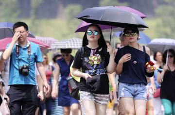 厳しい暑さの中、日傘を差して歩く外国人観光客ら=24日午前、東京都千代田区