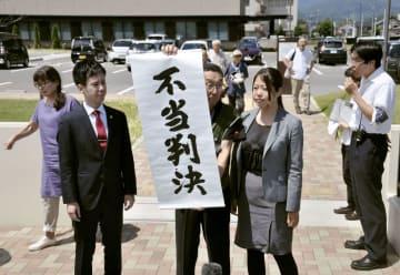 二審も敗訴となり、広島高裁松江支部前で「不当判決」の垂れ幕を掲げる原告側関係者=24日午後