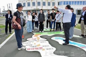 納沙布岬で歯舞群島の説明を聞く生徒ら=24日午後、北海道根室市