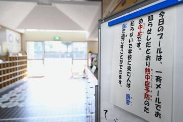 東京都新宿区立西新宿小の玄関に張られたプールの使用中止を知らせる紙=24日