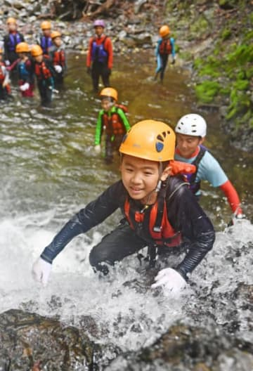 しぶきを上げて流れる滝を力強く登る子どもたち=24日、久慈市山形町・内間木川