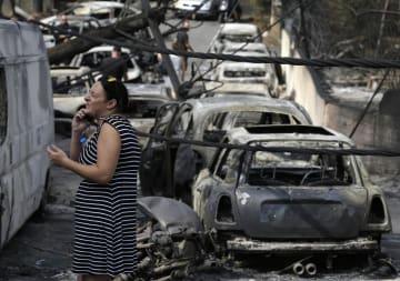 24日、ギリシャ・アテネ近郊マティで、焼け焦げた車の残骸が並ぶ中、立ち尽くす女性(AP=共同)