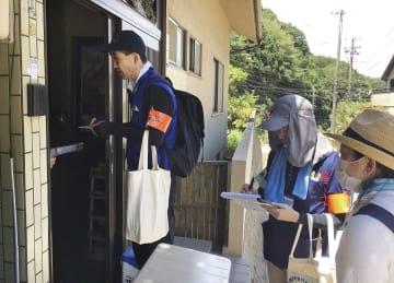広島県呉市の被害の大きかった地区で全戸訪問をする介護支援専門員ら=22日(日本介護支援専門員協会提供)