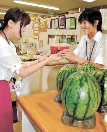 「あきた夏丸チッチェ」のおいしさを凝縮したスイカのフレッシュジュースを手に取る県職員