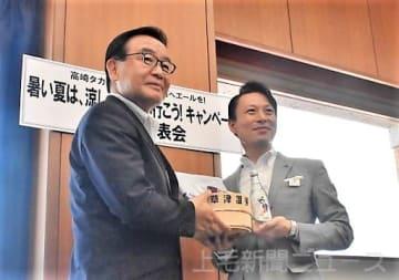 草津温泉グッズを持って記念撮影する(左から)黒岩町長、中川副店長