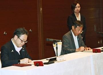 【中小企業の下請け条件の改善に向けた連携協定書に署名する世耕弘成経済産業相(左)と仁坂吉伸知事=和歌山市で】