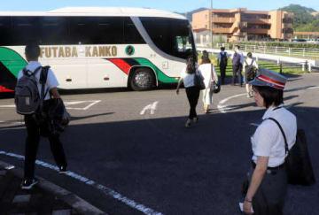 井原鉄道社員(手前右)が見守る中、三谷駅前で代行バスに乗り換える乗客たち