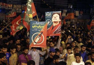 25日、パキスタン・イスラマバードで、イムラン・カーン党首が率いる野党第2党パキスタン正義運動(PTI)の下院選での勝利を伝える報道を受け、祝う支持者たち(AP=共同)