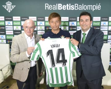 スペイン1部リーグのベティスに加入し、背番号「14」のユニホームを掲げる乾(中央)=26日、セビリア(同クラブ提供)