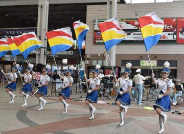 音楽隊の演奏に合わせて旗を振る県警カラーガード隊=JR長崎駅かもめ広場