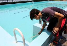 プール開放が中止になった妙法寺小学校で水温を確認する男性教諭=26日午前、神戸市須磨区妙法寺