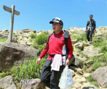 掃除用の水を運ぶ竹下友治さん(手前)と石丸武志さん。