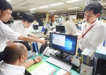 事務システムの完全復旧に向けて対応を協議する福井県坂井市職員=7月26日午後8時40分ごろ