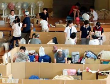 段ボールベッドなどが置かれた広島市安芸区の矢野南小体育館で過ごす被災者たち