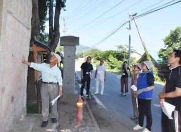 明治三陸大津波の供養塔などを巡り吉浜の歴史を解説する菊地正人分会長(左)