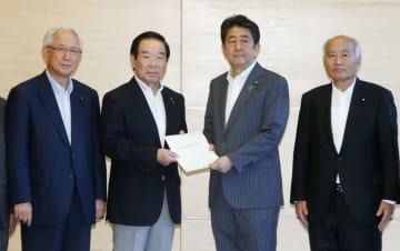 自民、公明両党から東日本大震災の復興加速化に向けた提言を受け取る安倍首相(中央右)=27日午後、首相官邸