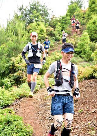 急な山の斜面を軽快に駆け下りるトレイルランの参加者たち(10日、高島市朽木)=市提供