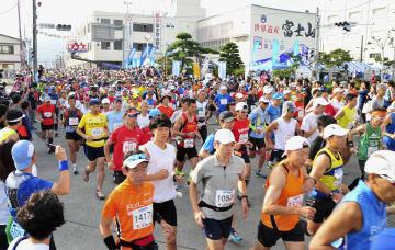 「富士登山競走」で山頂を目指しスタートするランナー=27日、山梨県富士吉田市役所