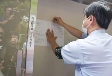 検察審査会の「不起訴相当」の議決書を張り出す関係者=27日午後、東京地裁
