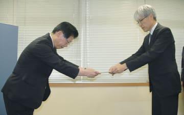 藤井直樹鉄道局長(右)から命令書を受け取るJR北海道の島田修社長=27日午後、国交省