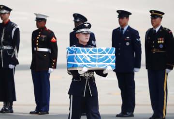 27日、韓国・ソウル南方の烏山米空軍基地で、米兵の遺骨が入った箱を運ぶ兵士(ロイター=共同)