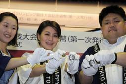 出来上がったばかりの記念貨幣を手にする正木健人選手(右)ら=27日午後、大阪市北区