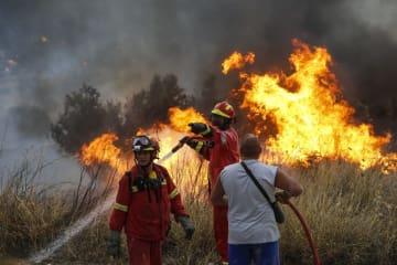 ギリシャの山林火災で、燃え上がる炎を消火する消防隊員=23日、アテネ(ゲッティ=共同)