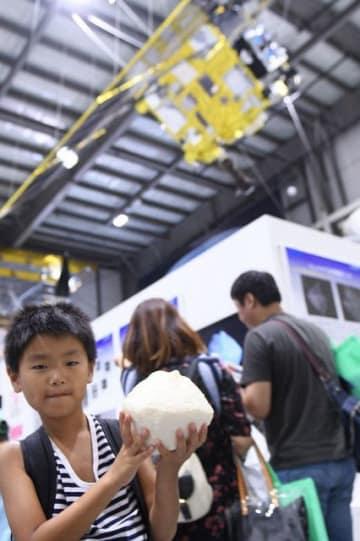 小惑星りゅうぐうの模型を手にする来場者。天井に飾られているのは実物大の「はやぶさ2」の模型=JAXA相模原キャンパス