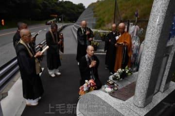 慰霊碑の前で読経する仏教会の僧侶