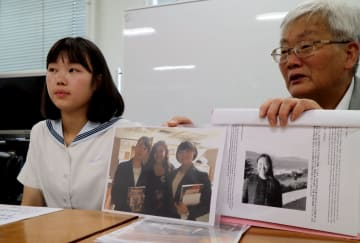 会見する平野さん(右)と中村さん。中央のカラー写真にはハワイ滞在中の野瀬さん(左端)と安野さん(右端)が写る=長崎市役所