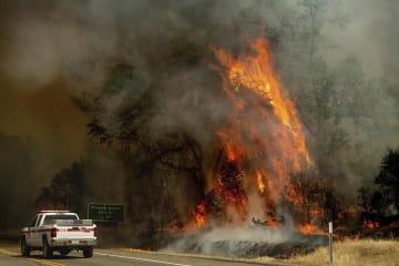 27日、米カリフォルニア州での山火事で道路に迫る火の手(AP=共同)