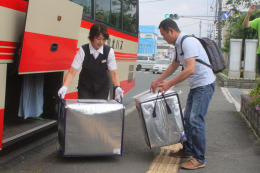 バス停でイチゴの保冷バッグを受け渡しするバス運転手(左)と洋菓子店の工場長