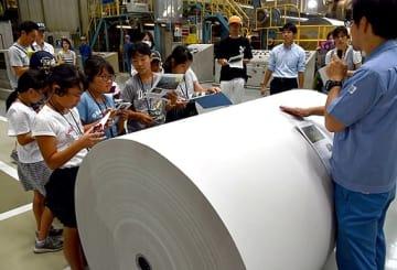 製造されたばかりの新聞用紙を前に説明を聞く子どもたち=28日、愛媛県四国中央市の大王製紙三島工場