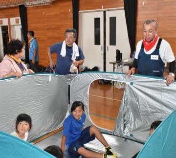 簡易間仕切りの設営と撤去を指導した千葉敏行さん(右)
