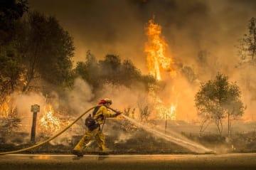 カリフォルニアの山火事、州中部イゴで消火にあたる消防士=28日(サクラメント・ビー・AP=共同)