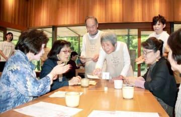 「注文をまちがえる料理店」でエプロン姿で接客する認知症の高齢者=5月、静岡県御殿場市の「とらや工房」