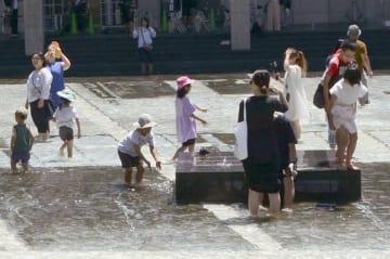 美術館の水場で涼を取る人たち=29日、新潟県十日町市