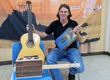 トロ箱ギターとスパニッシュギターを手にするスティーブン・フォークさん=阿久根市役所