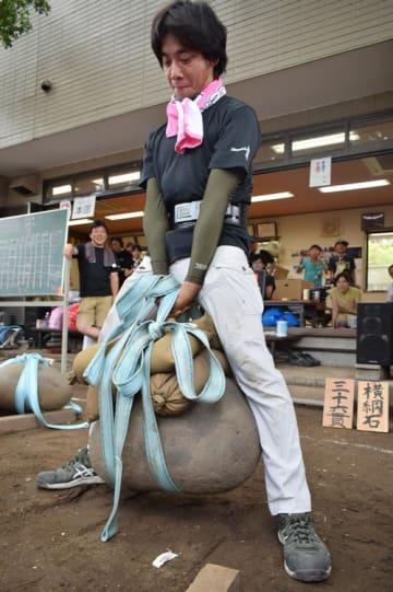 「さし石さんが大会」で約177キロの石を持ち上げ、大人の部個人戦で優勝した山下さん=29日、中央区の神明神社