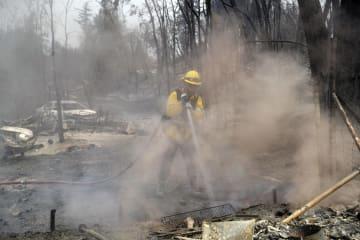 29日、米西部カリフォルニア州の山火事で放水する消防士(AP=共同)