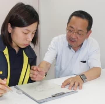 「培ってきた技術を後輩に伝えたい」と似顔絵捜査の指導をする渡辺巡査部長(右)