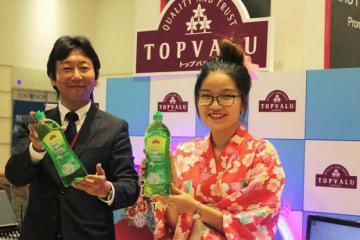 ベトナムで開発した新商品「肌に優しい食器用洗剤」を紹介するイオン・トップバリュ・ベトナムの塩谷社長(左)=30日、ホーチミン市