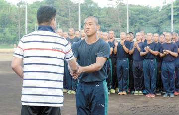 甲子園のベンチ入りメンバーを発表する浦和学院の森監督(左)と握手を交わす蛭間主将=30日、浦和学院グラウンド