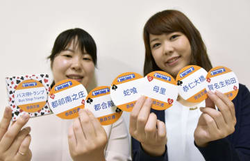 奈良交通が販売している難読停留所名のトランプを手にする福井佐也香さん(左)と小久保麻優さん=奈良市