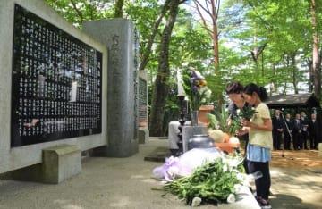 犠牲者の冥福を祈り、献花する参列者