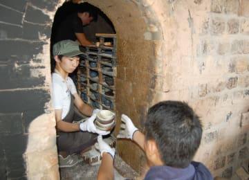 柿右衛門様式窯から作品を取り出す芸術学部の学生=福岡市東区の九州産業大学