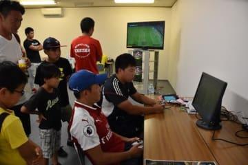 サッカーゲームで熱戦を繰り広げる参加者。試合の様子は会場のモニターにも映し出された=29日、勝浦市