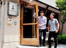 再利用したドアの前に立つ朴徹雄さん(左)と坂野雅さん(右)。「神戸は外国人と日本人がつくり上げたまち。僕もここから新しい歴史をつくりたい」と朴さん=神戸市灘区城内通4、ゲストハウス萬家