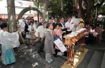 夏越祭で茅の輪をくぐり、無病息災を祈る参列者ら(31日午前10時30分、京都市東山区・八坂神社境内の疫神社)