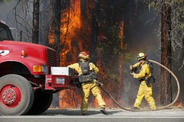米カリフォルニア州レディング近くで、高速道路付近の消火活動に当たる隊員=7月30日(ゲッティ=共同)